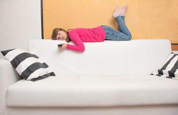 Una bambina annoiata sdraiata sul divano guarda la tv