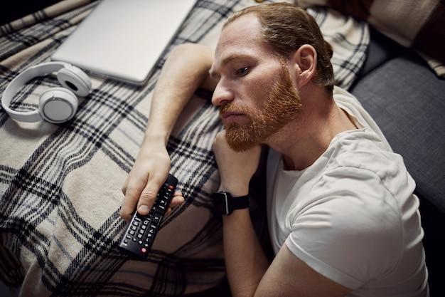 Uomo annoiato che guarda tv
