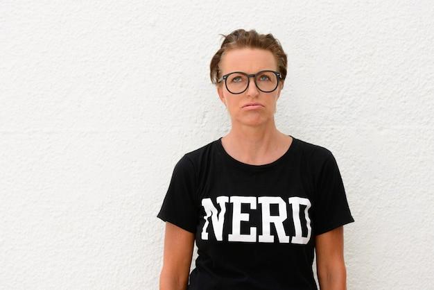 Donna matura annoiata del nerd che porta i grandi occhiali e che sta isolata
