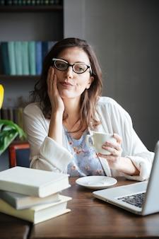 Donna matura annoiata in vetri che tengono tazza di tè e che esaminano macchina fotografica mentre sedendosi alla tavola con il computer portatile a casa