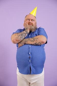 Annoiato uomo di mezza età con sovrappeso in camicia blu attillata e cappello da festa si appoggia sul palmo su sfondo viola in studio