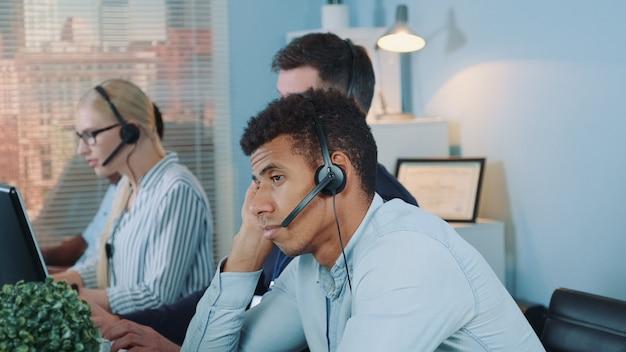 Operatore multietnico annoiato del servizio clienti che aspetta telefonata dal cliente.