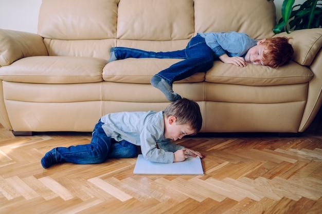 Fratelli annoiati a casa che giocano a vicenda sulla casa. stile di vita familiare al chiuso. bambini che fanno i compiti a terra senza scuola.