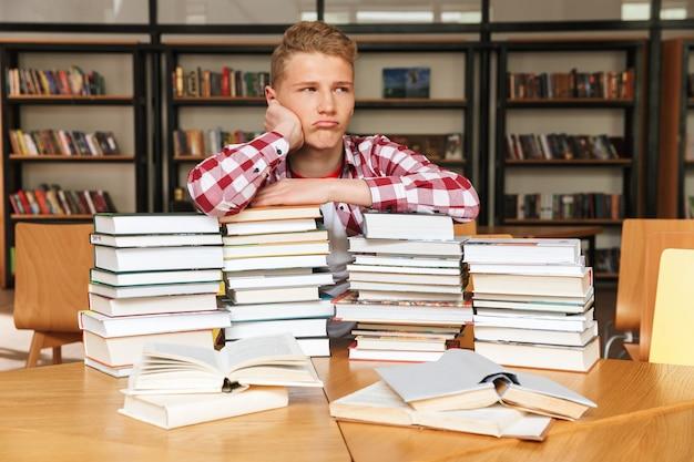 Annoiato adolescente seduto in biblioteca