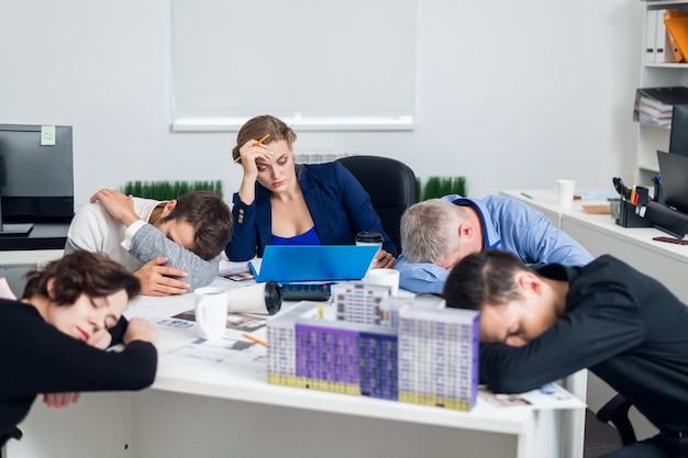Uomini d'affari annoiati o stanchi che dormono, riposando sul posto di lavoro durante la riunione