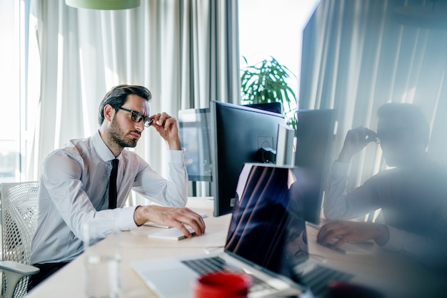 Uomo d'affari stanco annoiato che finisce il suo lavoro al suo posto di lavoro. concetto di ufficio.