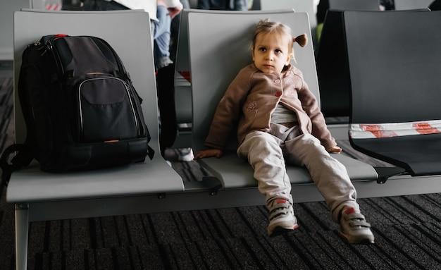 Bambino stanco annoiato nella sala d'attesa dell'aeroporto per i passeggeri