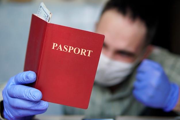 Un turista annoiato viene messo in quarantena a casa, indossando una maschera e guanti, guardando il passaporto e i soldi. i collegamenti aerei sono stati annullati a causa del coronavirus. vacanza annullata a causa della pandemia di covid-19