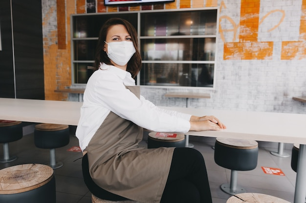 Una cameriera annoiata con indosso un grembiule e una maschera medica siede in un bar. il proprietario della caffetteria senza visitare i visitatori. attività commerciale.