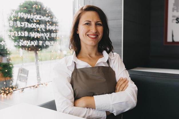 Una cameriera annoiata in grembiule siede in un bar. il proprietario della caffetteria senza visitare i visitatori. attività commerciale.