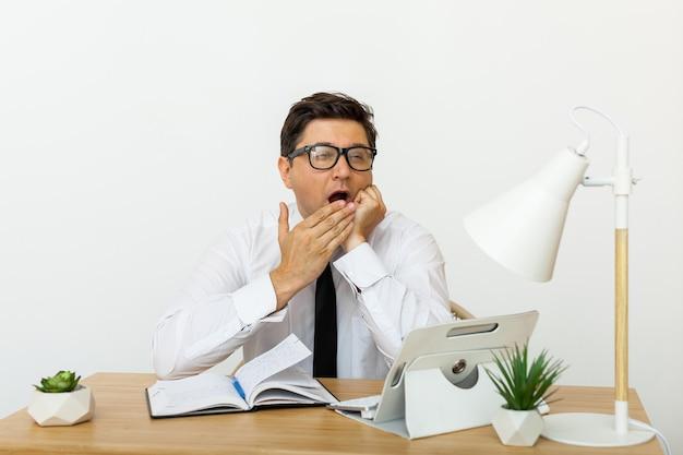 Annoiato al concetto di lavoro, lavoratore maschio non motivato stanco che perde tempo sul posto di lavoro