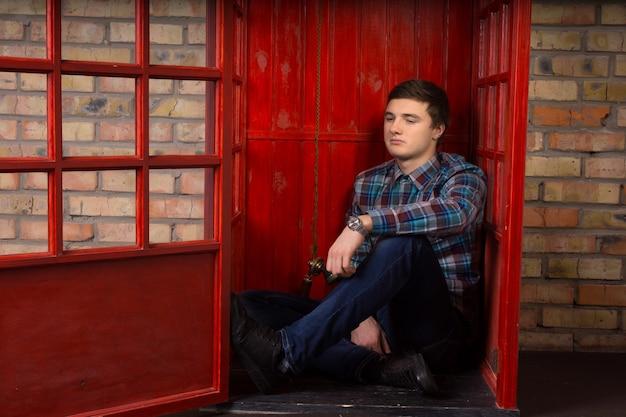 Giovane annoiato in attesa di una telefonata su un telefono pubblico a pagamento seduto sul pavimento della cabina con un'espressione svogliata