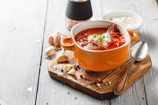 Zuppa tradizionale ucraina e russa di borsch con carne, barbabietole e cavolo. zuppa di carne in una ciotola arancione.