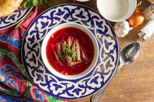 Borscht con panna acida. zuppa ucraina tradizionale di manzo, barbabietola, cavolo e erbe aromatiche in un piatto con un motivo nazionale uzbeko