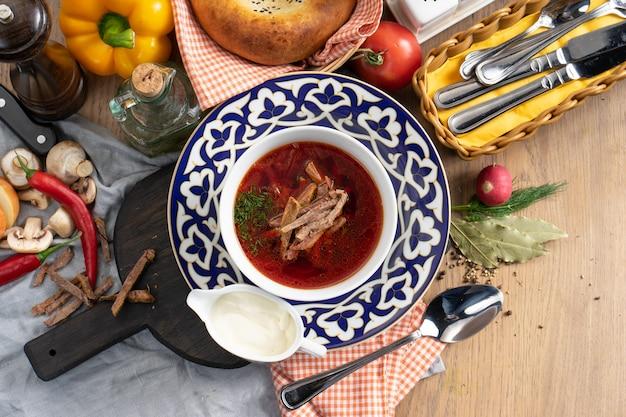 Borscht con panna acida - una zuppa ucraina tradizionale a base di verdure e carne di manzo in un piatto con un tradizionale uzbeko