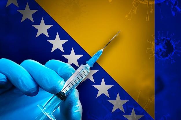 Bosnia ed erzegovina vaccinazione covid19 la mano in un guanto di gomma blu tiene la siringa nella bandiera