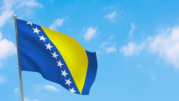Bandiera della bosnia ed erzegovina in pole. cielo blu. bandiera nazionale della bosnia ed erzegovina