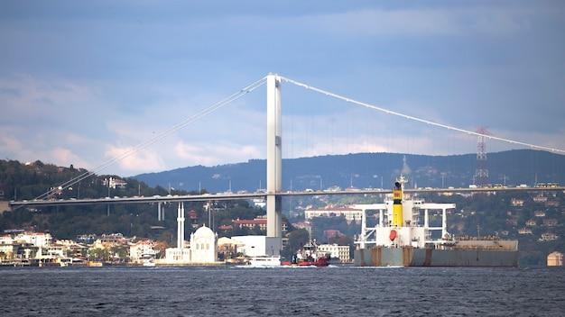 Lo stretto del bosforo e il ponte con le navi che galleggiano sotto di esso, la moschea e gli edifici situati sulle colline e vicino alla riva, istanbul, turchia