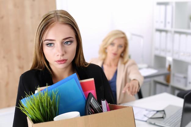 Capo che licenzia un dipendente. impiegato licenziato sconsolato che trasporta una scatola piena di effetti personali.