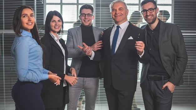 Capo e squadra felice di affari che stanno nell'ingresso dell'ufficio. il concetto di lavoro di successo