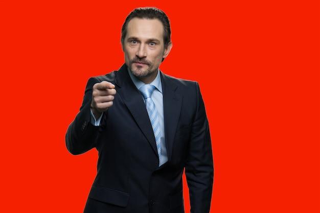 Il capo ti sta indicando per costringerti a fare qualcosa. isolato su sfondo rosso.