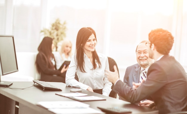 Capo e membri del team aziendale seduti sul posto di lavoro sullo sfondo dell'ufficio