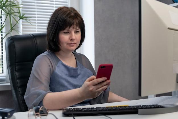 Capo sul posto di lavoro con il telefono in mano. la donna di affari decide le edizioni di affari. il segretario è distratto mentre lavora.