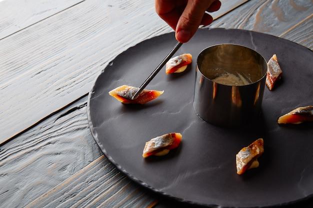 Preparazione di sarde bota con mano dello chef