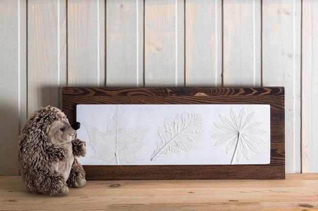 Intonaco botanico acero, lupino, foglia di quercia di immagini scultoree 3d su mensola in legno in interni in stile scandinavo.