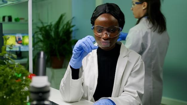 Scienziato ricercatore botanico che analizza un campione di liquido verde al microscopio per esperimenti di microbiologia. specialista chimico che scopre piante ogm organiche mentre lavora in un laboratorio farmaceutico