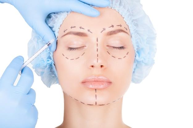 Iniezione di botox. attraente giovane donna in copricapo medico e schizzi sul viso tenendo gli occhi chiusi mentre i medici fanno un'iniezione in faccia