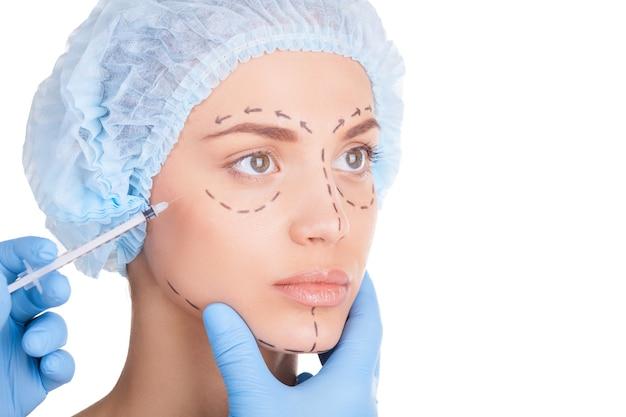 Iniezione di botox. bella giovane donna in copricapo medico e schizzi sul viso che guarda lontano mentre i medici fanno un'iniezione in faccia