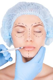 Iniezione di botox nelle labbra. bella giovane donna in copricapo medico e schizzi sul viso tenendo gli occhi chiusi mentre i medici fanno un'iniezione nelle labbra