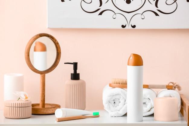Bottiglia di deodorante per ambienti, asciugamani e cosmetici sul tavolo in bagno