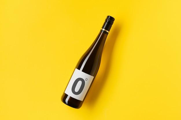 Bottiglia di vino bianco rosso senza alcol su sfondo giallo