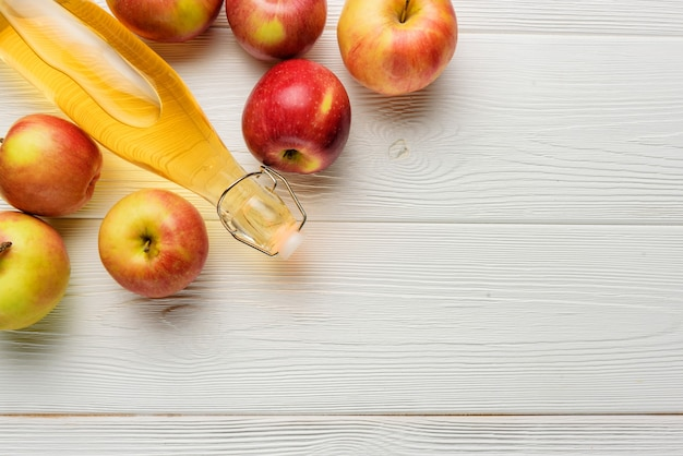 Una bottiglia di aceto di mele o succo con mele su uno sfondo bianco con spazio di copia. composizione piatta con sidro di mele in un primo piano di una bottiglia di vetro.