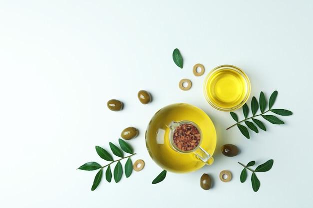 Bottiglia e ciotola di olio, olive e ramoscelli su bianco