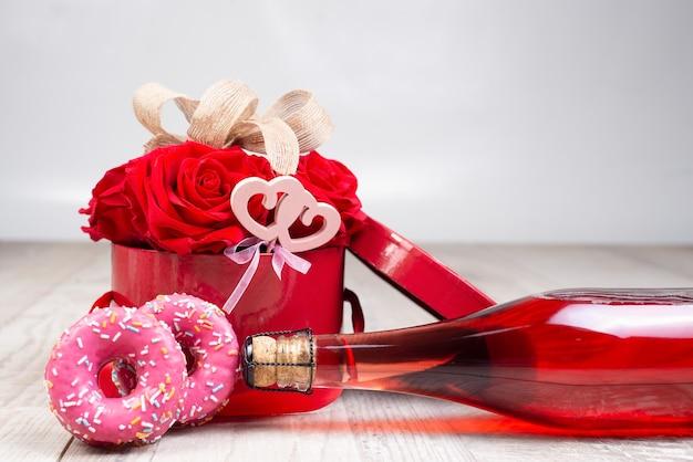 Bottiglia di champagne, scatola con rose, nastro rustico, ciambelle su una superficie di legno. festivo