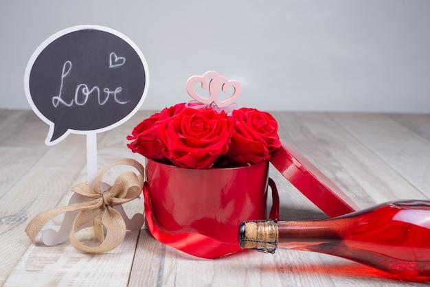 Bottiglia di champagne, scatola con rose e stand la scritta - amore, legata con un fiocco rustico su una superficie di legno.