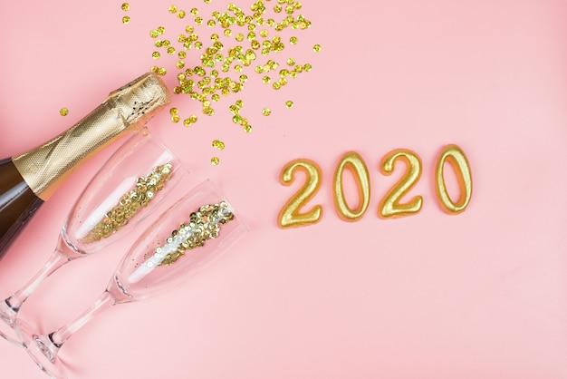 Bottiglia di champagne, bicchieri trasparenti con coriandoli d'oro e numeri d'oro su un pastello rosa