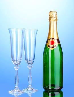 Bottiglia di champagne e calici su blu