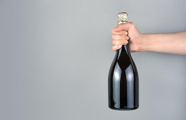 Bottiglia di champagne sulla mano di un uomo