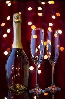 Bottiglia di champagne e due bicchieri vuoti nel bokeh di capodanno