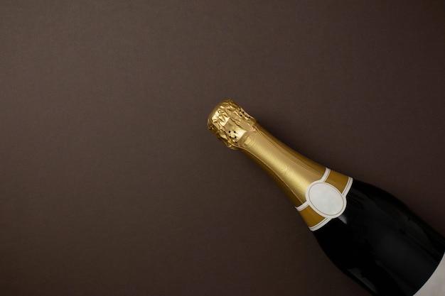 Bottiglia di champagne con etichetta dorata in bianco su sfondo marrone scuro con spazio di copia.