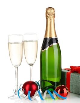 Bottiglia di champagne con bicchieri e palle di natale isolate su bianco