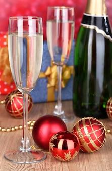 Bottiglia di champagne con bicchieri e palle di natale su un tavolo di legno su sfondo rosso