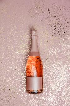Bottiglia di champagne con glitter oro rosa sfondo, vista dall'alto