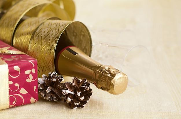 La bottiglia di champagne con nastro oro lucido e confezione regalo rossa. felice anno nuovo e buon natale concetto. copia spazio