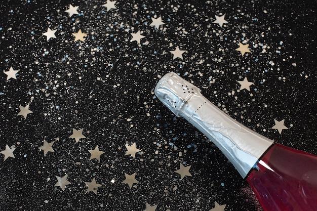 Bottiglia di champagne con coriandoli stella sdraiato sul nero