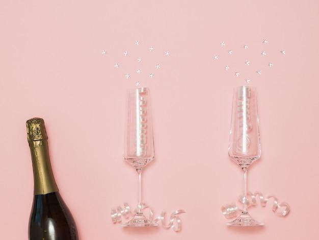 Una bottiglia di champagne con due bicchieri con scintille volanti su uno sfondo rosa. sfondo festivo con bicchieri di champagne.